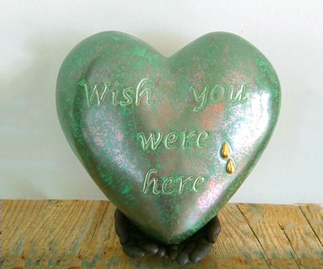 urn waarbij bronzen handen een hart dragen van keramiek.