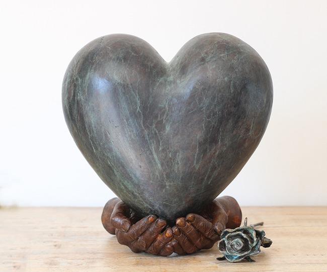 Een bronzen urn waarbij handen een hart dragen.